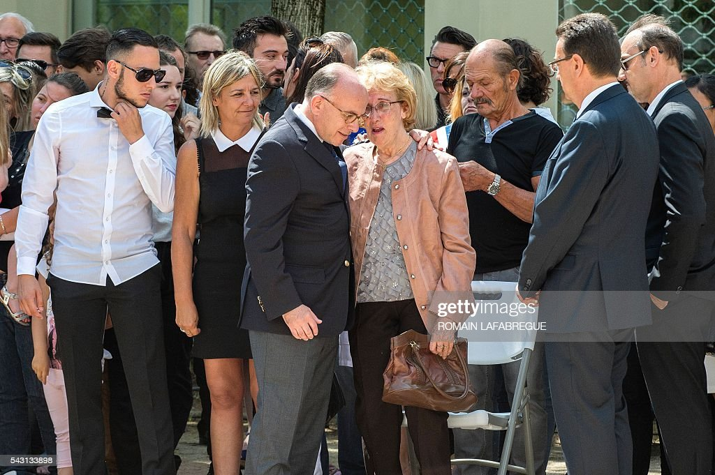 French Interior Minister Bernard Cazeneuve (C) comforts Herve Cornara's mother Lucette as the wife Laurence (2nd L) and son Kevin (L), attend a memorial ceremony on June 26, 2016 in Fontaines-sur-Saone, in tribute to Herve Cornara, killed one year ago in a terror attack at the Air Products factory in Saint-Quentin-Fallavier. In June, 2015, Yassin Salhi beheaded Herve Cornara, owner of a company where he had worked near Lyon. / AFP / ROMAIN