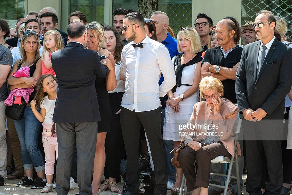 French Interior Minister Bernard Cazeneuve (L) comforts Herve Cornara's wife Laurence as the son Kevin (3rd R), the mother Lucette (2nd R) and the brother Didier Cornara (R) attend a memorial ceremony on June 26, 2016 in Fontaines-sur-Saone, in tribute to Herve Cornara, killed one year ago in a terror attack at the Air Products factory in Saint-Quentin-Fallavier. In June, 2015, Yassin Salhi beheaded Herve Cornara, owner of a company where he had worked near Lyon. / AFP / ROMAIN