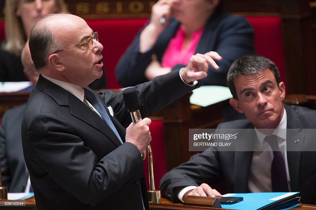 French Interior minister Bernard Cazeneuve delivers a speech as Prime minister Manuel Valls listens during a session of Questions to the government, on May 4, 2016 at the French National Assembly in Paris. / AFP / BERTRAND