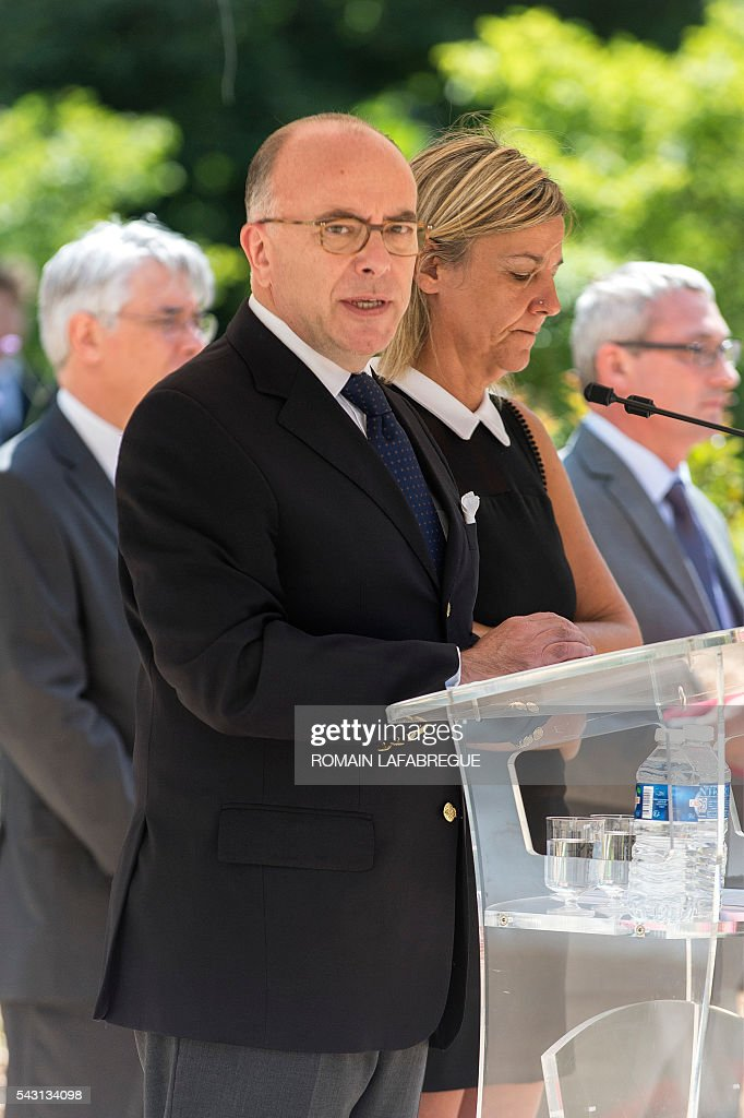 French Interior Minister Bernard Cazeneuve (L), flanked by Herve Cornara's wife Laurence (R), delivers a speech during a memorial ceremony on June 26, 2016 in Fontaines-sur-Saone, in tribute to Herve Cornara, killed one year ago in a terror attack at the Air Products factory in Saint-Quentin-Fallavier. In June, 2015, Yassin Salhi beheaded Herve Cornara, owner of a company where he had worked near Lyon. / AFP / ROMAIN