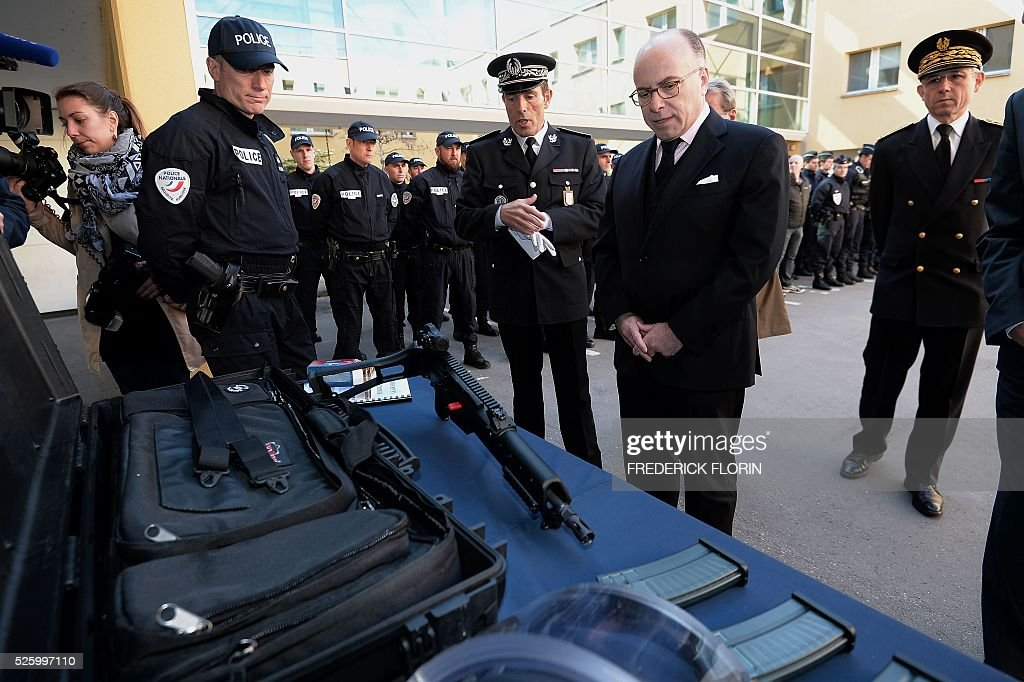 French Interior Minister Bernard Cazeneuve (2nd R) looks at weapons during a visit to Strasbourg, eastern France, on April 29, 2016. / AFP / FREDERICK