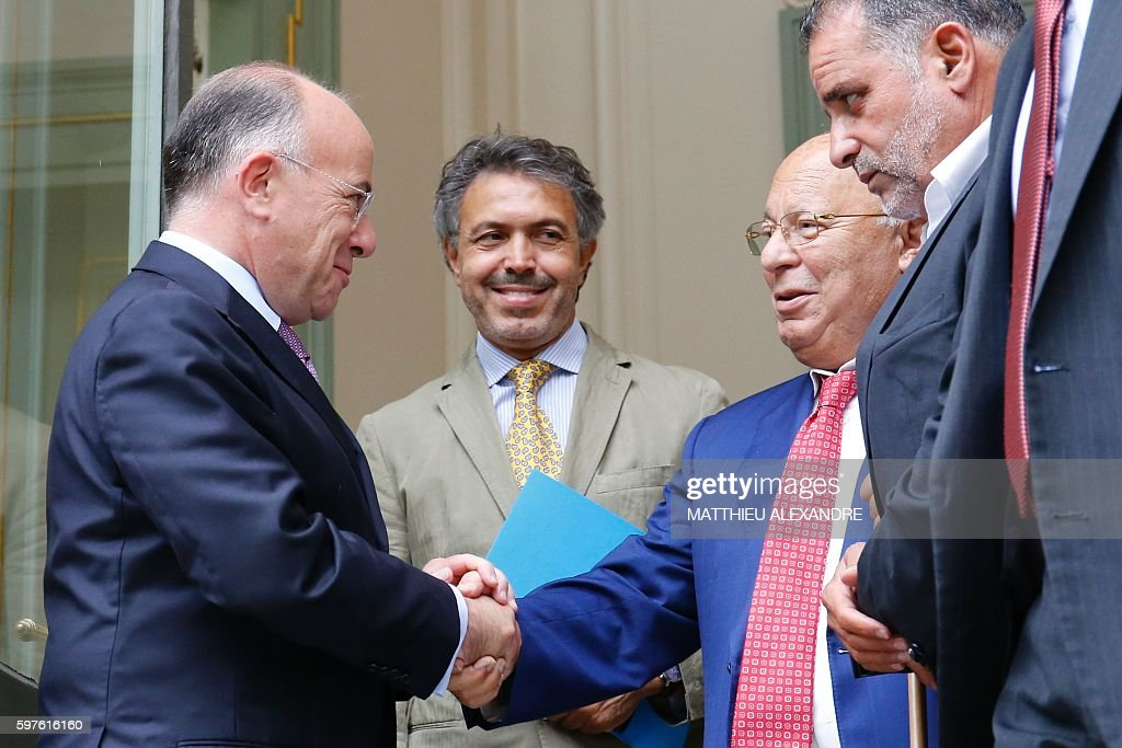 French Interior Minister Bernard Cazeneuve shakes hands with Paris' Mosque Rector Dalil Boubakeur following a meeting with representatives of the...