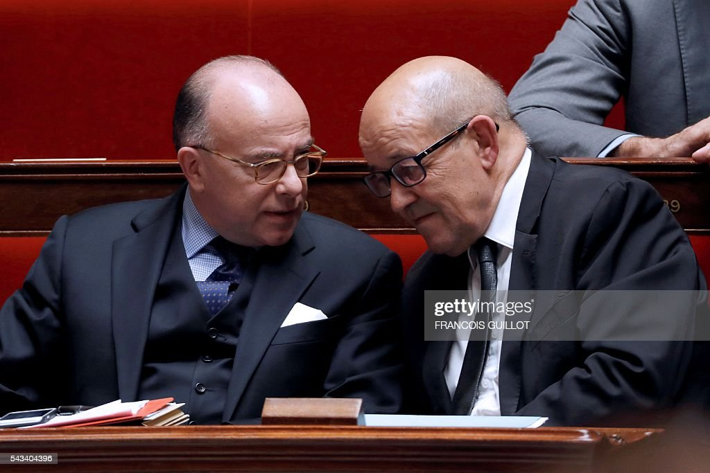 French Interior minister Bernard Cazeneuve (L) speaks with French Defence minister Jean-Yves Le Drian (R) during the questions to the government session on June 28, 2016 at the French National Asssembly in Paris. / AFP / FRANCOIS
