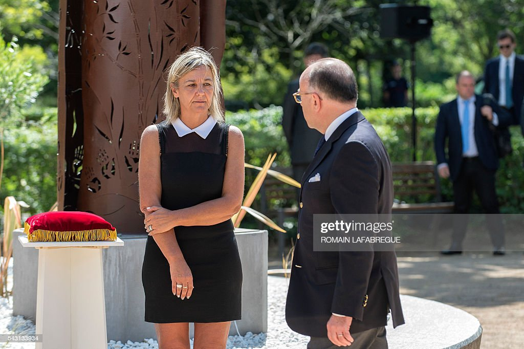 French Interior Minister Bernard Cazeneuve (R) speaks with Herve Cornara's wife Laurence (L), during a memorial ceremony on June 26, 2016 in Fontaines-sur-Saone, in tribute to Herve Cornara, killed one year ago in a terror attack at the Air Products factory in Saint-Quentin-Fallavier. In June, 2015, Yassin Salhi beheaded Herve Cornara, owner of a company where he had worked near Lyon. / AFP / ROMAIN
