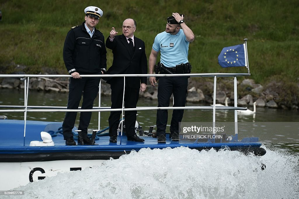 French interior Minister Bernard Cazeneuve stands in front of a French Gendarmerie boat sailing on a river of Strasbourg, eastern France on April 29, 2016. / AFP / FREDERICK