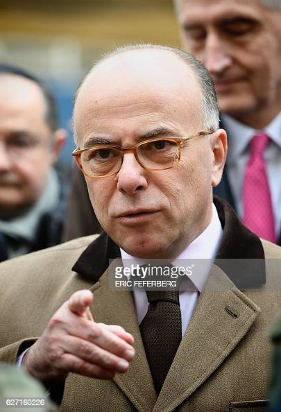 French Interior Minister Bernard Cazeneuve talks with a police chief as part of a visit focused on security measures at Jewish schools on December 2...
