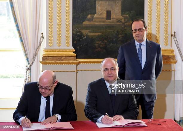 French Interior Minister Bruno Le Roux and French Secretary of State for Development and Francophonie JeanMarie Le Guen sign while France's President...