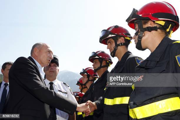 French Interior Minister Gerard Collomb shakes hands with French firemen brigade fighting against wilde fires in Palneca during a visit on August 5...