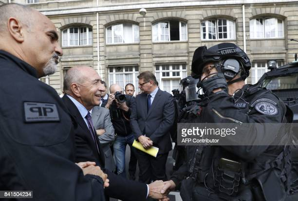 French Interior Minister Gerard Collomb shakes hands with members of the Research and Intervention Brigade of the French national police next to BRI...