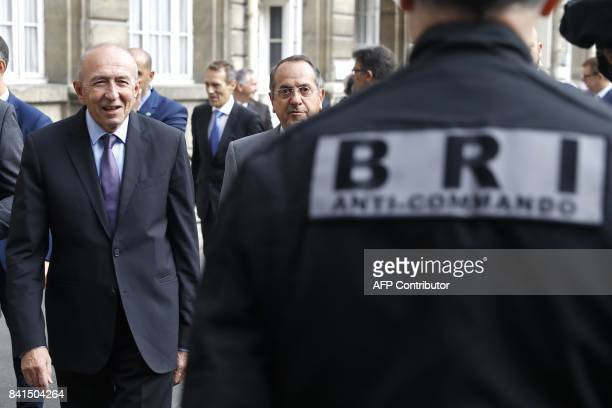 French Interior Minister Gerard Collomb walks towards a member of the Research and Intervention Brigade of the French national police next to Paris...