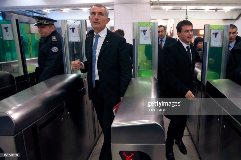 French Interior Minister Manuel Valls (R) and France's national rail company SNCF head, Guillaume Pepy enter in the RER station on December 28, 2012 at the Gare de Lyon in Paris. AFP PHOTO JOEL SAGET