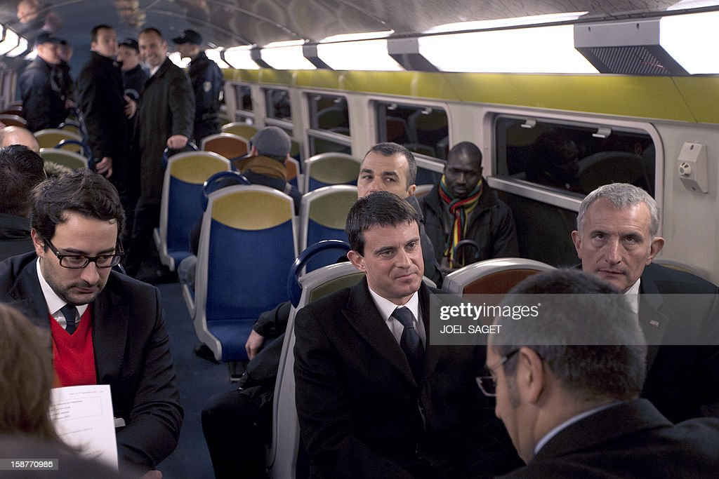 French Interior Minister Manuel Valls (C) and France's national rail company SNCF head, Guillaume Pepy (R) sit in a RER train (Regional Express Network), on December 28, 2012 at the Gare de Lyon in Paris.