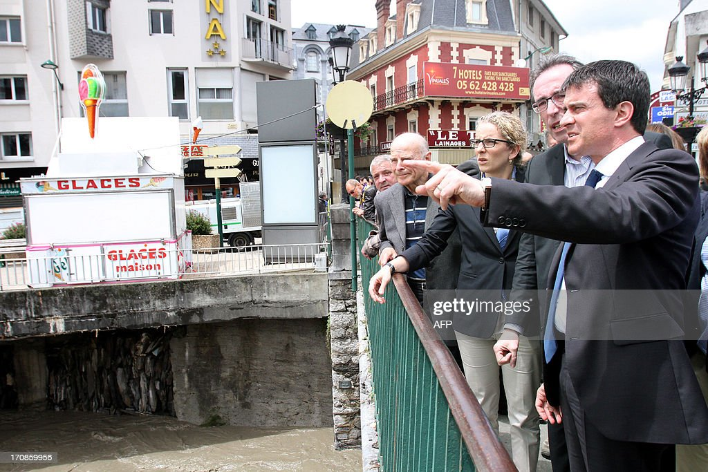 French Interior Minister Manuel Valls (R) and French Ecology, Sustainable Development and Energy Delphine Batho (C) visit Lourdes, southwestern France, on June 19,2013, following heavy rainfalls. Flash floods in southwestern France claimed two elderly victims in the space of 24 hours and forced the inundated grotto at Lourdes to remain closed for a second day, officials said on June 19. The region has been lashed by unseasonal storms since June 18 and more than 2,000 people have had to be evacuated from their homes, some of them by helicopter.