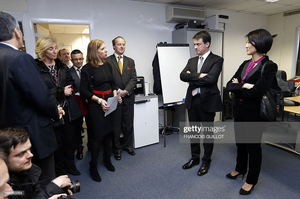 French Interior Minister Manuel Valls (2ndR) and French Junior Minister for SMEs, Innovations and Digital Economy Fleur Pellerin (R) listen to explanations during their visit to the central office of the IT and cyber crime police unit (known in French as the O.C.L.C.T.I.C.), on January 11, 2013 in Nanterre, outside Paris.