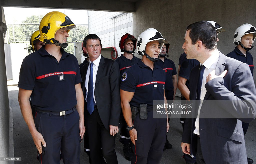 French Interior Minister Manuel Valls (2ndL) and French Junior Minister for Social and Solidarity Economy Benoit Hamon (R) meet firefighters during a visit at a police station in Trappes, a suburb of Paris, on July 22, 2013. Violent clashes erupted between citizens and French police near Trappes' police station late on July 18, 2013, after police officers carried out an identity check on a full-face veiled woman and her husband. The woman's husband tried to strangle one of the officers during the check according to Versailles' prosecutor Vincent Leclous on July 20. The situation was still tense in front of the police station on the evening of July 21, where a group of people challenged the police before being dispersed by backup units.