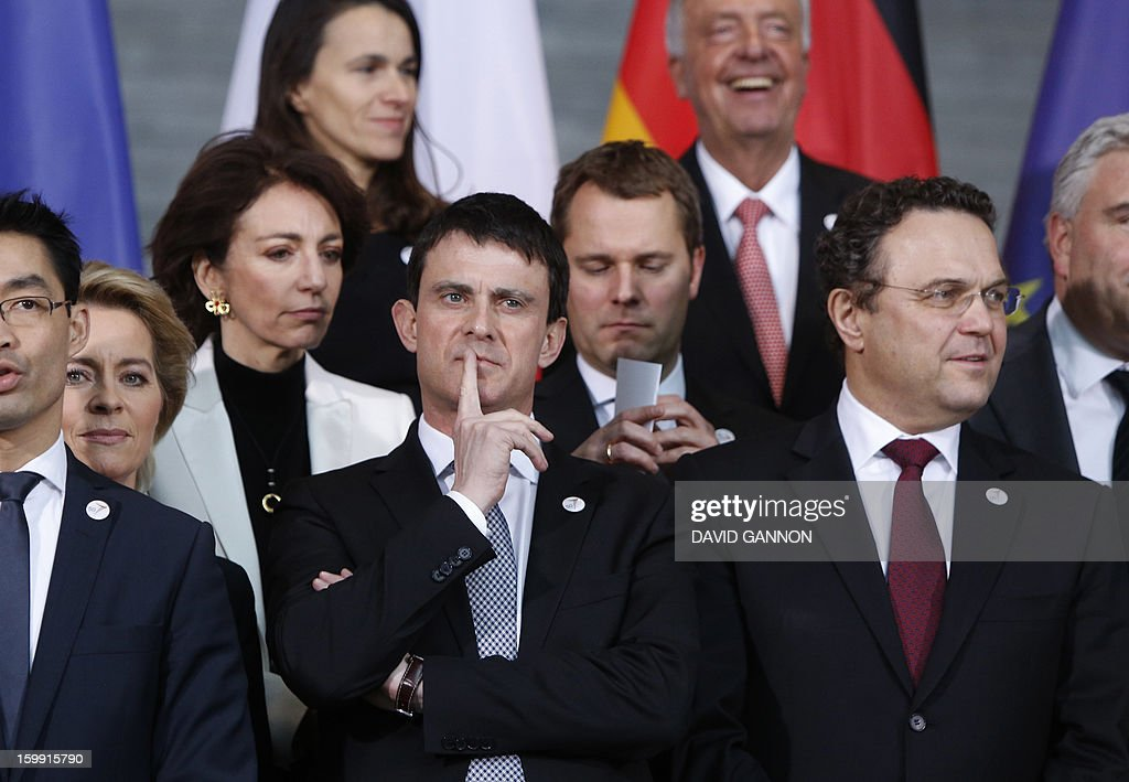 French Interior minister Manuel Valls (C) and German Interior Minister Hans-Peter Friedrich (front R) line up with members of French and German governments for a family picture prior to the Franco-German cabinet meeting on January 22, 2013 in Berlin, Germany as part of the celebrations marking the 50th anniversary of the Elysee Treaty , a French-German cooperation launched after WWII. In signing the landmark treaty on January 22, 1963, then French president Charles de Gaulle and West German chancellor Konrad Adenauer sealed a new era of reconciliation between the former foes which has since driven European unity. AFP PHOTO / DAVID GANNON