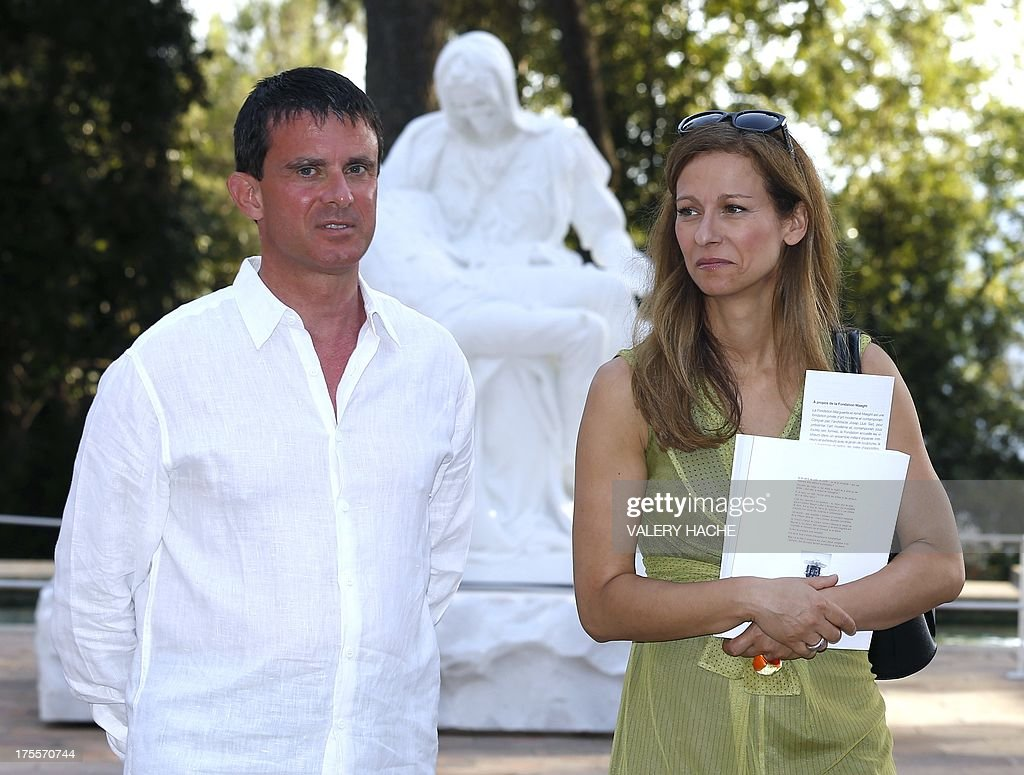 French Interior Minister Manuel Valls (L) and his wife Anne Gravoin pose as they visit on August 4, 2013, in Saint-Paul-de-Vence, southeastern France, an exhibition at the 'Fondation Maeght' entitled 'Adventures of truth - Painting and philosophy : a narrative' (Les Aventures de la verite....) which runs until November 11, 2013.