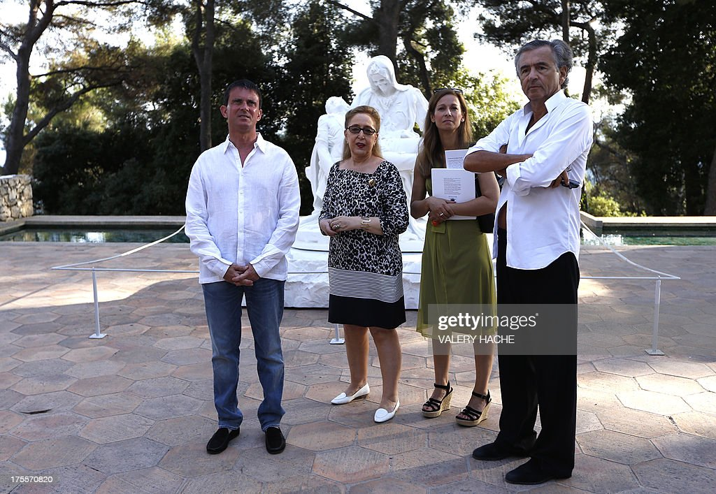 French Interior Minister Manuel Valls (L) and his wife Anne Gravoin (2ndR) pose with French philosopher and writer Bernard-Henri Levy (R) as they visit on August 4, 2013, in Saint-Paul-de-Vence, southeastern France, the exhibition organized by the author at the 'Fondation Maeght'. Levy is the artistic curator for the exhibition entitled 'Adventures of truth - Painting and philosophy : a narrative' (Les Aventures de la verite....) which runs until November 11, 2013. second lefdt, Isabelle Maeght, Maeght Foundation's director and daughter of Adrien Maeght who created the foundation.