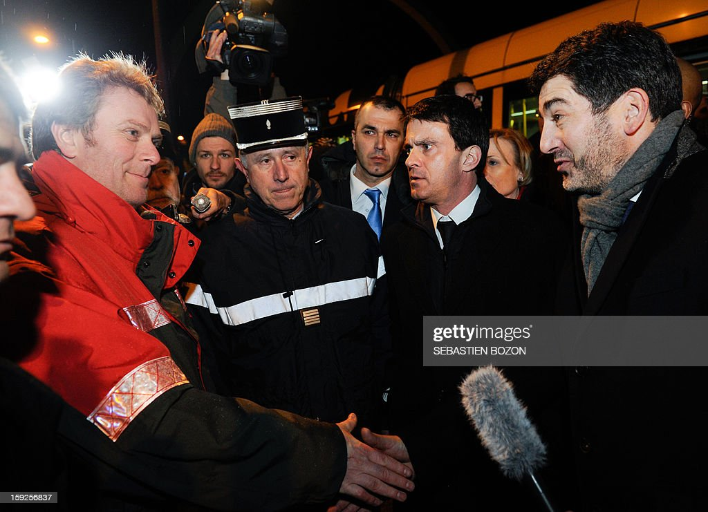 French Interior Minister Manuel Valls (2nd R) and Mulhouse's Mayor Jean Rottner (R) talk with an agent of the Solea tramway services in Les Coteaux, a district of Mulhouse, on January 10, 2013. The district of 'Les Coteaux ' is one of 49 'Zone de Sécurité Prioritaire' (ZSP) ('Priority Security Zones') where the fight against criminality and violence are a major issue. Many cars were burnt in the district during the new year's celebration on December 31, 2012, and youths threw a few Molotov cocktails at a tramway on January 5, 2013.