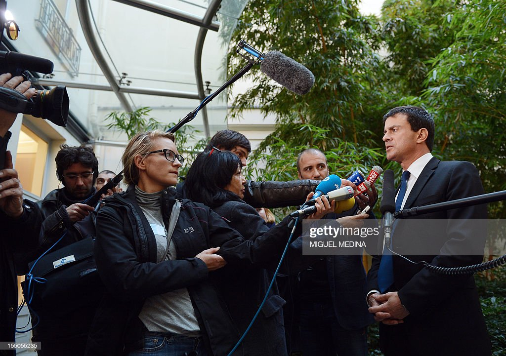 French Interior Minister, Manuel Valls (R) answers journalists' questions upon his arrival to the French Senate, on October 31, 2012 in Paris, after France expelled a Tunisian imam accused of anti-Semitism and of calling his followers to 'violent jihad' and violence against women, the interior ministry said. AFP PHOTO / MIGUEL MEDINA