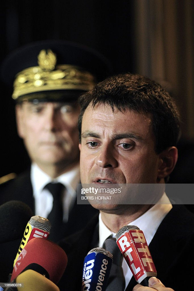 French Interior Minister Manuel Valls (C) answers journalists' questions after a meeting with local police representatives on November 26, 2012 in Marseille, southeastern France, after a 47-year old man was shot dead today by two unidentified people who stole his briefcase.