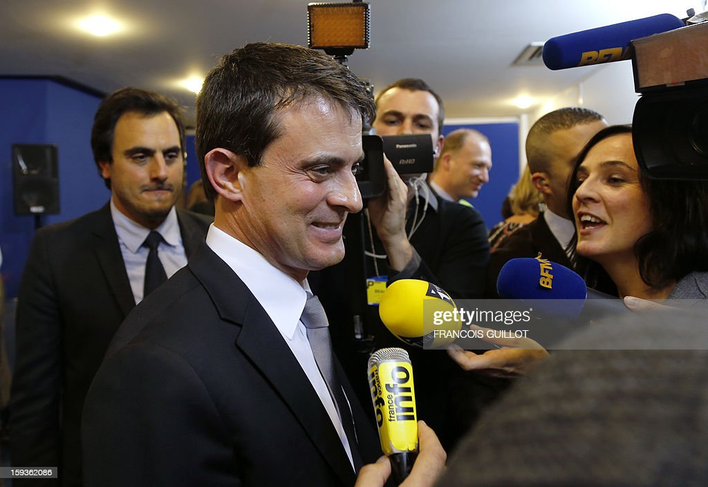 French Interior Minister Manuel Valls (C) answers journalists' questions during his visit to the central office of the IT and cyber crime police unit (known in French as the O.C.L.C.T.I.C.), on January 11, 2013 in Nanterre, outside Paris. AFP PHOTO FRANCOIS GUILLOT