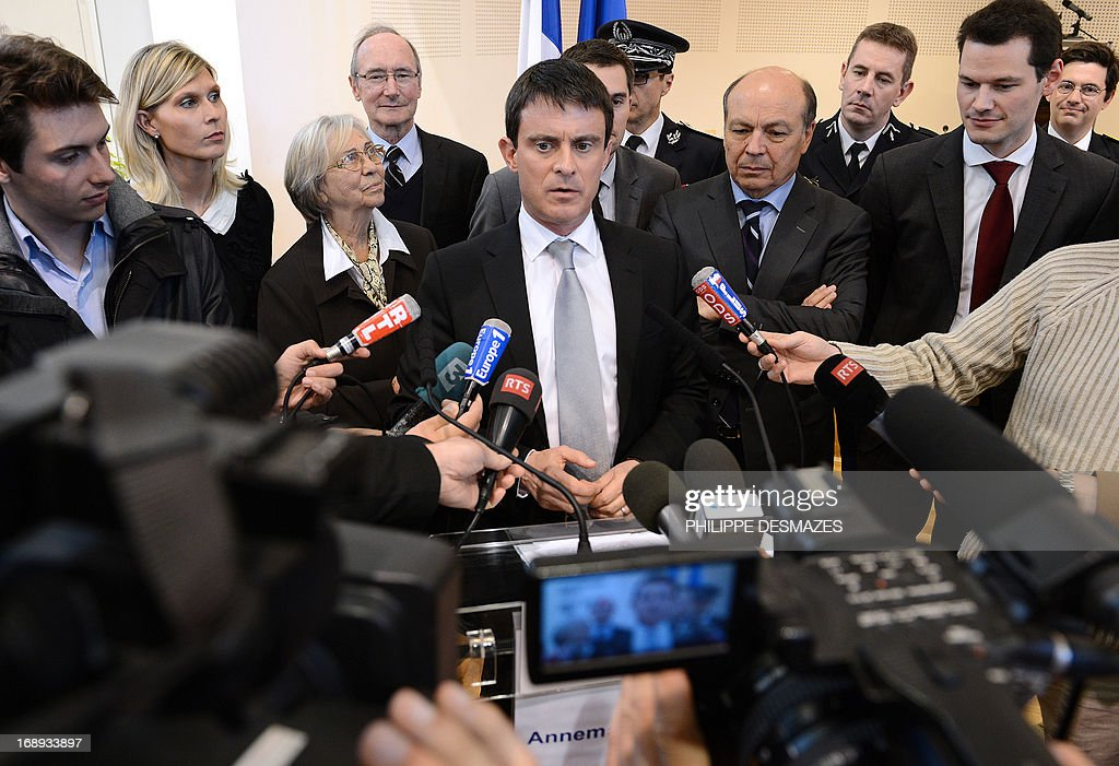 French Interior Minister Manuel Valls (C) answers journalists' questions on May 17, 2013 in Annemasse after his visit to a police station in a priority areas of critical security (ZSP). AFP PHOTO/PHILIPPE DESMAZES