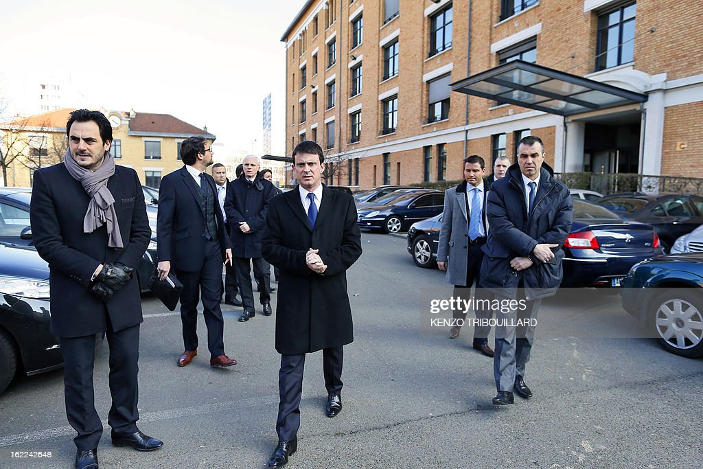 French Interior minister Manuel Valls (C) arrives to talk to journalists on February 21, 2013 in Paris, after an accident following a car chase between policemen and suspects driving a SUV vehicle, killing two policemen earlier in the morning at the Porte de la Chapelle.