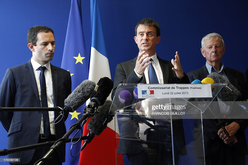 French Interior Minister Manuel Valls (C), beside French Junior Minister for Social and Solidarity Economy Benoit Hamon (L) and Trappes mayor Guy Malandain (R), speaks during a press conference at a police station in Trappes, a suburb of Paris, on July 22, 2013. Violent clashes erupted between citizens and French police near Trappes' police station late on July 18, 2013, after police officers carried out an identity check on a full-face veiled woman and her husband. The woman's husband tried to strangle one of the officers during the check according to Versailles' prosecutor Vincent Leclous on July 20. The situation was still tense in front of the police station on the evening of July 21, where a group of people challenged the police before being dispersed by backup units.