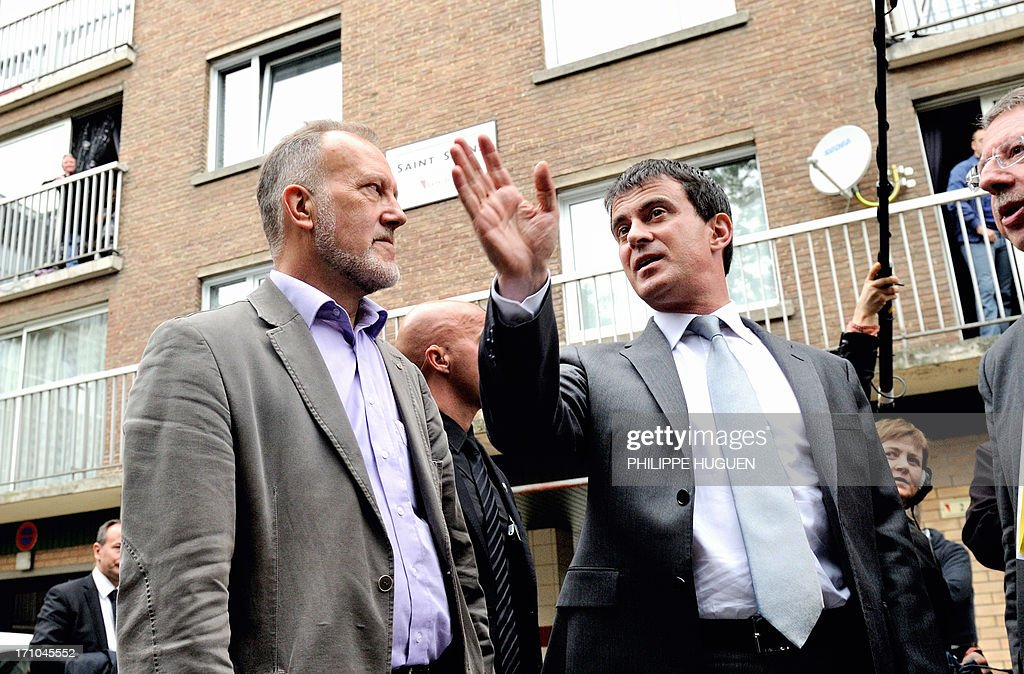 French Interior Minister Manuel Valls (R) chats with an unidentified man on June 21, 2013 during a visit to a priority area of critical security (ZSP) at the Mousserie district in Wattrelos, northern France.