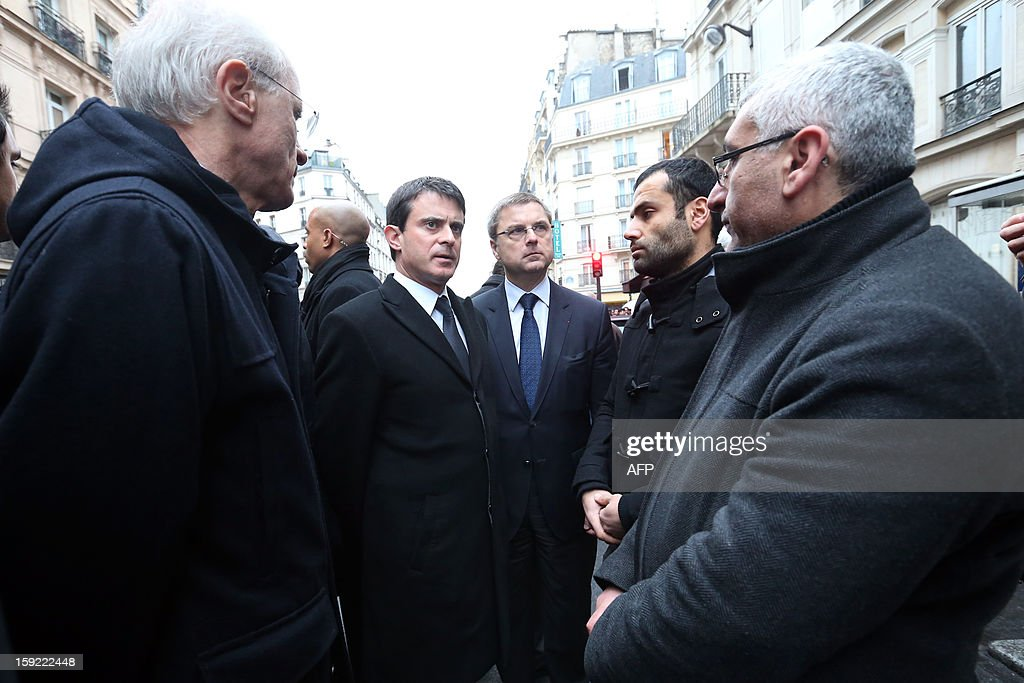 French Interior Minister Manuel Valls (2ndL), flanked by Police Prefect Bernard Boucault (L) and the director of the French Police Christian Flaesch (C), speaks with the representative of the Kurdish association 'Academy of Arts and Culture' (2ndR, no name available) on January 10, 2013, near the Kurdistan Information Bureau in Paris where three Kurdish women were found killed with a gunshot to the head. The bodies of the women were found shortly before 2:00 am (0100 GMT) inside the building in the 10th arrondissement of the French capital. One of the women was 32-year-old Fidan Dogan who worked in the institute's information centre, according to its director, Leon Edart. The identities of the other two women, who were reportedly Kurdish activists but did not work at the Institute, were not immediately available. AFP PHOTO / THOMAS SAMSON