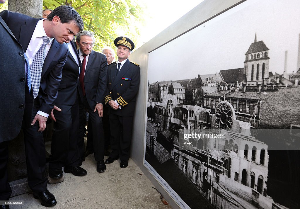French Interior Minister Manuel Valls (L) flanked by Strasbourg's Mayor Roland Ries (2ndL) looks at a photograph showing Strasbourg's synagogue destroyed on September 12, 1940 by the Nazis, after unveiling a plaque dedicated to the 'Righteous among the Nations' ('Justes parmi les nations' in French) for their efforts to save Jews from the Nazis in World War II, on July 22, 2012 in Strasbourg, eastern France, as part of a ceremony to commemorate the seventieth anniversary of the Vel D'Hiv roundup (Rafle du Vélodrome d'Hiver). Center, Alsace region and Bas-Rhin department's Prefect Pierre-Etienne Bisch.