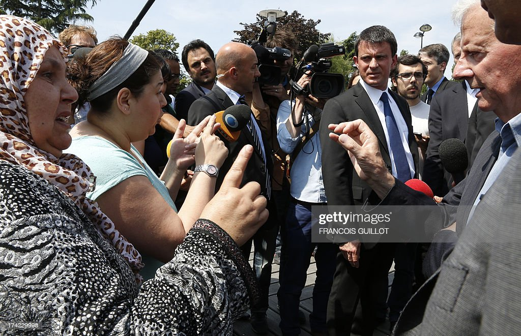 French Interior Minister Manuel Valls (2ndR), flanked by Trappes mayor Guy Malandain (R), listens to inhabitants on July 22, 2013 in Trappes, a suburb of Paris. Violent clashes erupted between citizens and French police near Trappes' police station late on July 18, 2013, after police officers carried out an identity check on a full-face veiled woman and her husband. The woman's husband tried to strangle one of the officers during the check according to Versailles' prosecutor Vincent Leclous on July 20. The situation was still tense in front of the police station on the evening of July 21, where a group of people challenged the police before being dispersed by backup units.