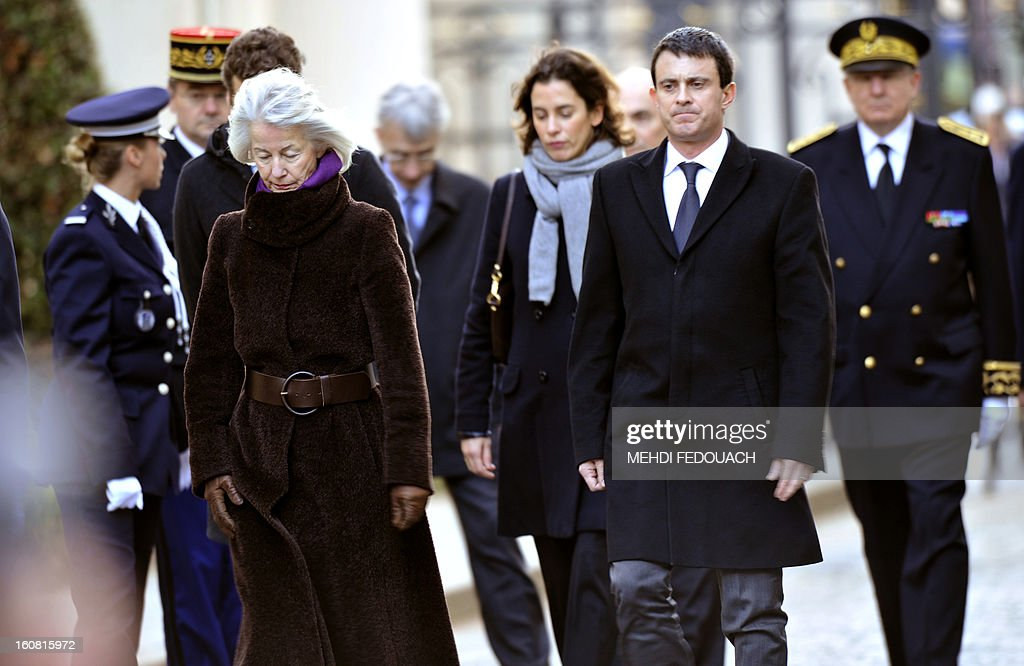 French Interior minister Manuel Valls (R) follows late prefect Claude Erignac's widow during a tribute ceremony 15 years after he was murdered, on February 6, 2013 at the Interior ministry in Paris. Erignac, 60, the state-appointed 'prefect' or governor of Corsica, was shot three times in the back of the head as he walked to a concert hall in Corsica's capital Ajaccio on February 5, 1998, the most spectacular attack in some 30 years of separatist violence. AFP PHOTO / MEHDI FEDOUACH