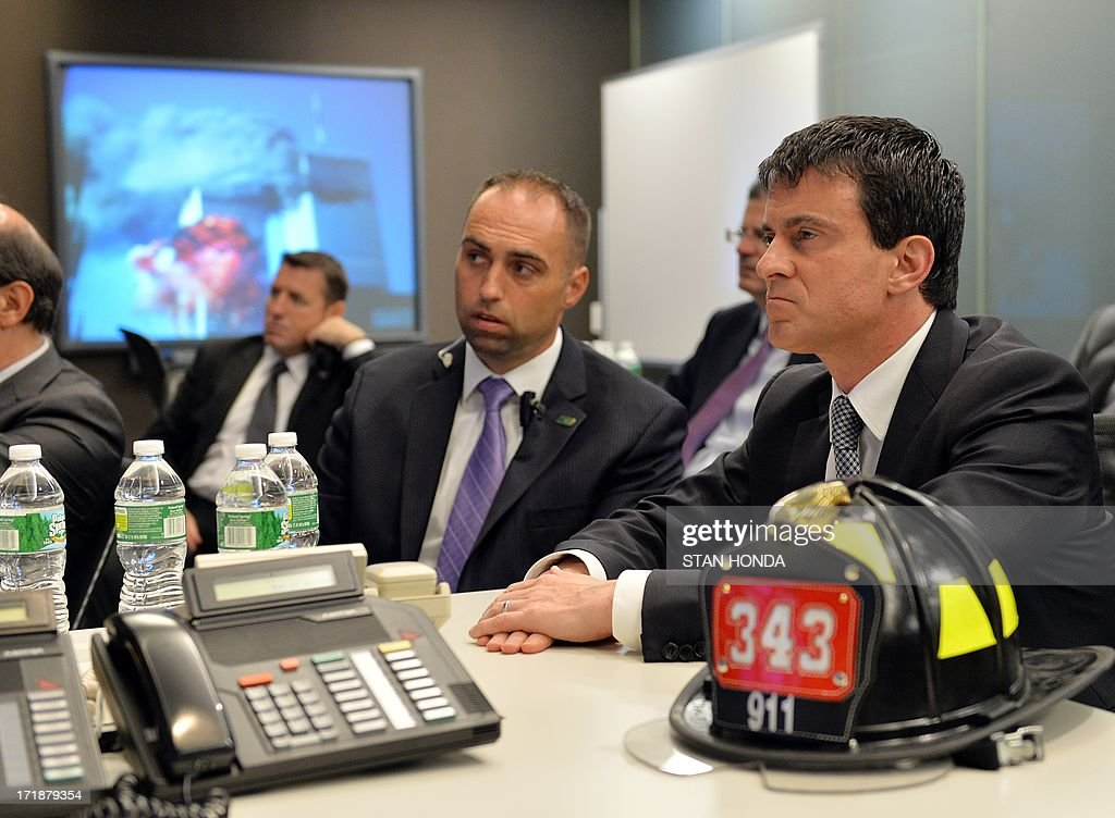 French Interior Minister Manuel Valls (R) gets a briefing at New York City Fire Department headquarters about the September 11, 2001 attacks on the World Trade Center (picture on monitor) June 29, 2013 in the Brooklyn borough of New York. The firefighter helmet representing the 343 firefighters lost in the attacks was presented to Vallas by Fire Department Commissioner Salvatore Cassano. AFP PHOTO/Stan HONDA