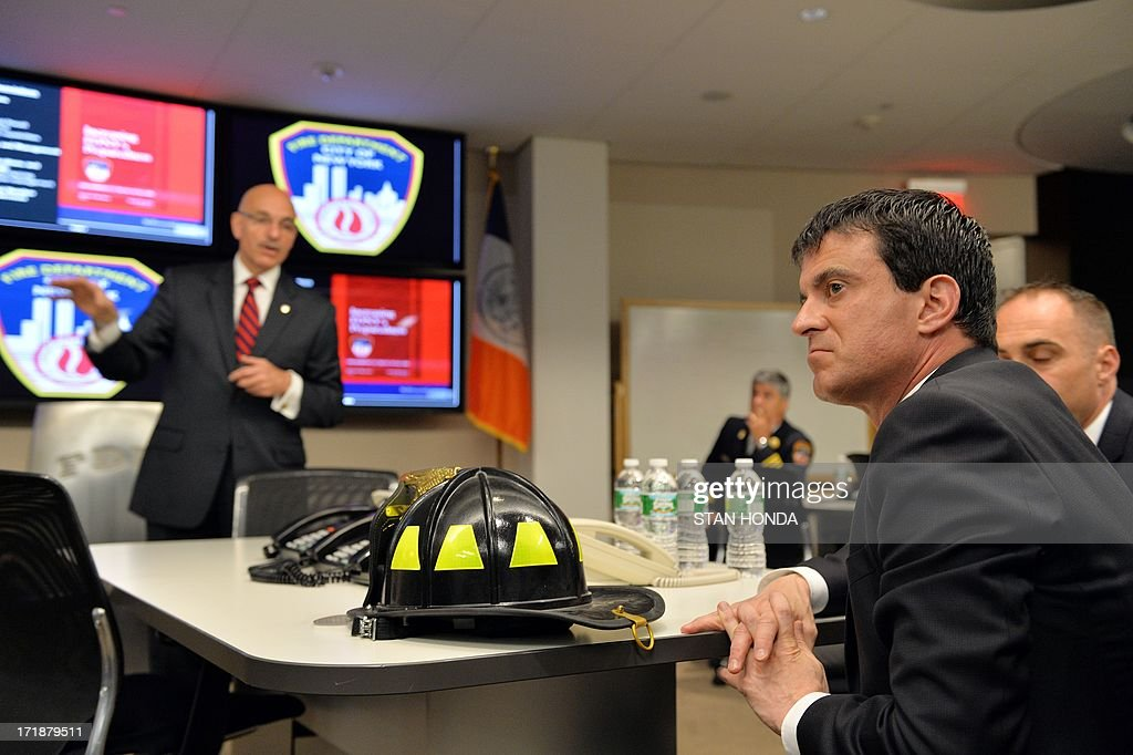 French Interior Minister Manuel Valls (R) gets a briefing by New York City Fire Department Commissioner Salvatore Cassano (L) about the September 11, 2001 attacks on the World Trade Center June 29, 2013 in the Operations Center at fire department headquarters in the Brooklyn borough of New York. The fire fighter helmet representing the 343 firefighters lost in the attacks was presented to Vallas by Commissioner Cassano. AFP PHOTO/Stan HONDA