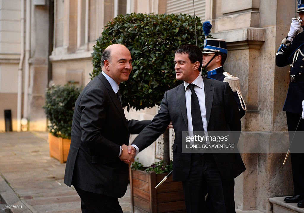 French Interior Minister Manuel Valls (R) greets Economy, Finance and Foreign Trade Minister <a gi-track='captionPersonalityLinkClicked' href=/galleries/search?phrase=Pierre+Moscovici&family=editorial&specificpeople=667029 ng-click='$event.stopPropagation()'>Pierre Moscovici</a> prior to the traditional breakfast organized at the Ministry of Interior at the beginning of the New Year, on January 3, 2014 in Paris. AFP PHOTO LIONEL BONAVENTURE