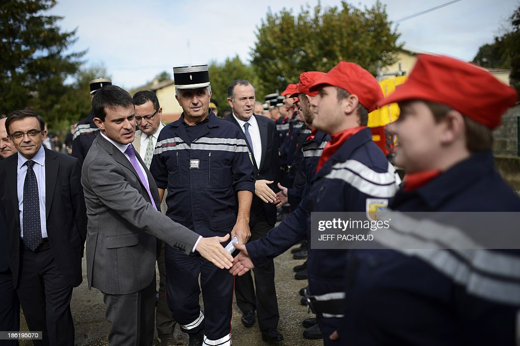 French Interior Minister Manuel Valls (2ndL) greets firefighters on October 29, 2013 during a visit in Clerieux, southeastern France, where villagers were sinistered by floods following heavy rains. AFP PHOTO / JEFF PACHOUD
