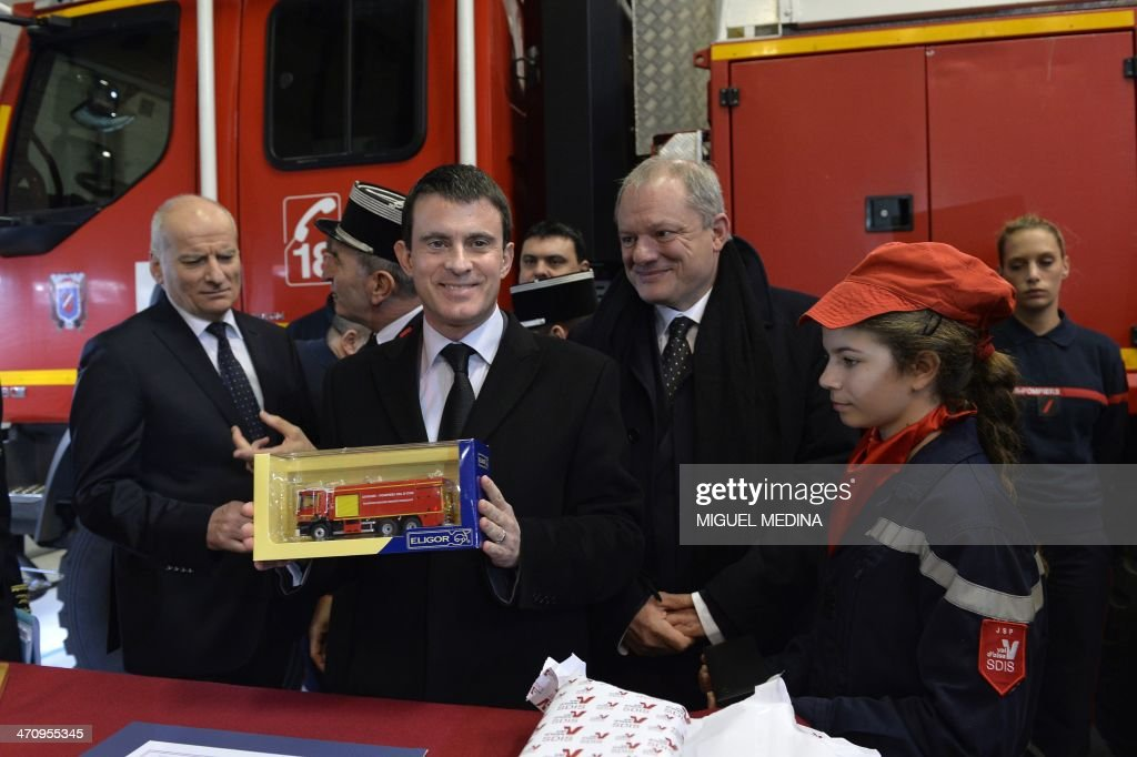 French Interior minister Manuel Valls (C) holds a toy firefighter vehicle as he visits a fire station in Magny-en-Vexin, 60 kms northeast of Paris, on February 21, 2014.