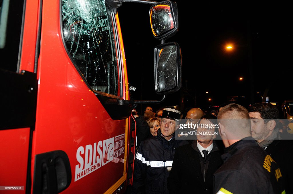 French Interior Minister Manuel Valls (3rd R) inspects damage to a firetruck as he discusses with firemen in Les Coteaux, a district of Mulhouse, on January 10, 2013. The district of 'Les Coteaux ' is one of 49 'Zone de Sécurité Prioritaire' (ZSP) ('Priority Security Zones') where the fight against criminality and violence are a major issue. Many cars were burnt in the district during the new year's celebration on December 31, 2012, and youths threw a few Molotov cocktails at a tramway on January 5, 2013. AFP PHOTO / SEBASTIEN BOZON