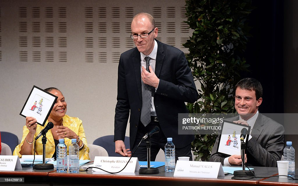 French Interior Minister, Manuel Valls (R) jokes with French Justice Minister Christiane Taubira (L) and the president of the Union Syndicale des Magistrats Christophe Regnard (C) as they attend the annual congress of the Union Syndicale des Magistrats (union association of magistrates), in Colmar, eastern France, on October 19, 2012.