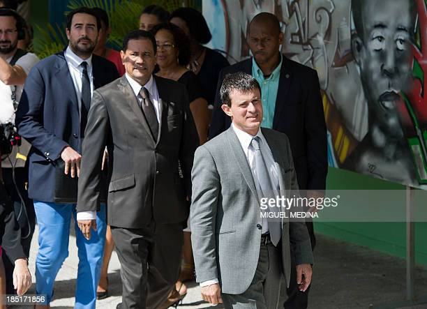 French Interior Minister Manuel Valls leaves after a visit at the 'Frantz Fanon' school on October 17 2013 in La Trinite on the French Caribbean...
