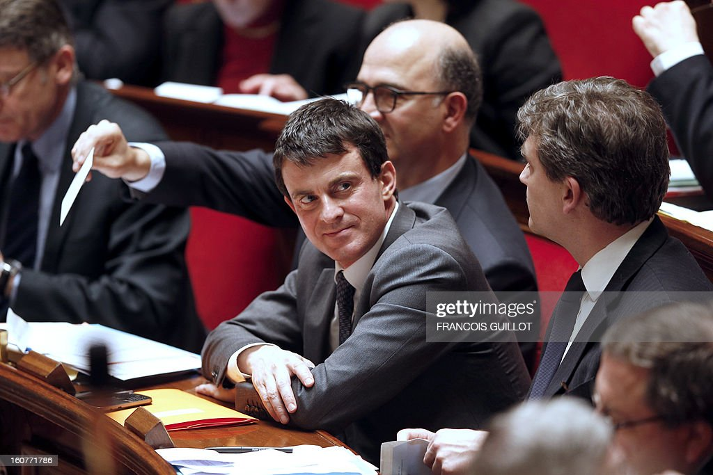 French Interior Minister Manuel Valls (C) listens during a session of questions to the government at the National Assembly on February 5, 2013 in Paris. AFP PHOTO FRANCOIS GUILLOT