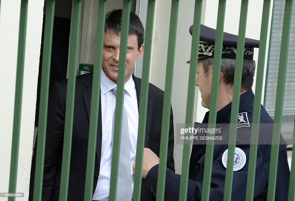 French Interior Minister Manuel Valls (L) listens to a police officer as he leaves after visiting a police station in a priority areas of critical security (ZSP) in Annemasse on May 17, 2013.