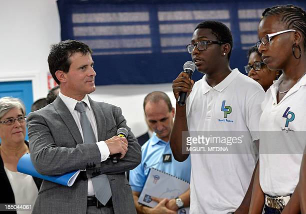 French Interior Minister Manuel Valls listens to a student as he visits the 'Frantz Fanon' school on October 17 2013 in La Trinite on the French...