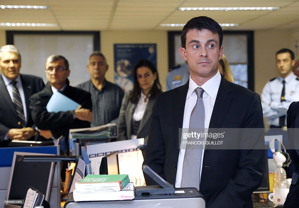 French Interior Minister Manuel Valls (R) listens to explanations during his visit to the central office of the IT and cyber crime police unit (known in French as the O.C.L.C.T.I.C.), on January 11, 2013 in Nanterre, outside Paris. AFP PHOTO FRANCOIS GUILLOT