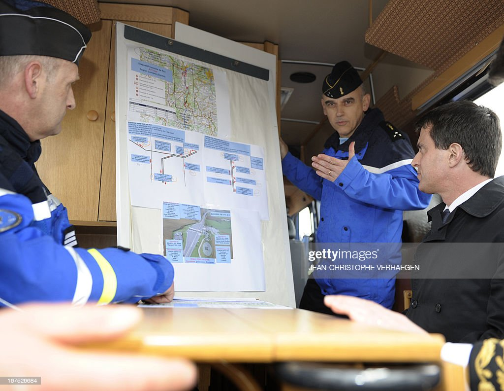 French Interior Minister Manuel Valls (R) listens to General Jean-Regis Vechambre (2ndR), commander of the gendarmerie for the Lorraine region giving explanations on the police operation with a map during a control by the French customs, police and gendarmerie at the highway toll of Gye on April 26, 2013, during a visit of the department of Meurthe-et-Moselle, eastern France. VERHAEGEN