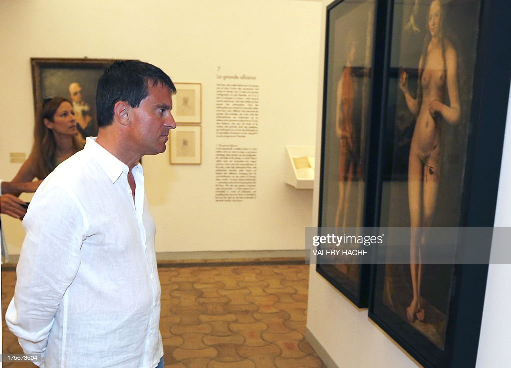 French Interior Minister Manuel Valls looks at a painting representing 'Adam and Eve' by Italian artist Lucas Cranach the eleder as he visits his wife Anne Gravoin on August 4, 2013, in Saint-Paul-de-Vence, southeastern France, an exhibition at the 'Fondation Maeght'. French philosopher and writer Bernard-Henri Levy is the artistic curator for the exhibition entitled 'Adventures of truth - Painting and philosophy : a narrative' (Les Aventures de la verite....) which runs until November 11, 2013.