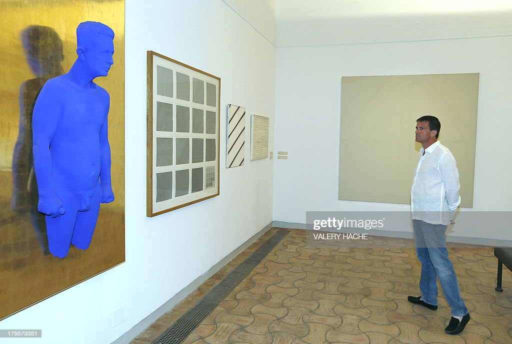 French Interior Minister Manuel Valls looks at a work of French artist Yves Klein, 'Portrait-relief de Claude Pascal' as he visits on August 4, 2013, in Saint-Paul-de-Vence, southeastern France, an exhibition at the 'Fondation Maeght'. French philosopher and writer Bernard-Henri Levy is the artistic curator for the exhibition entitled 'Adventures of truth - Painting and philosophy : a narrative' (Les Aventures de la verite....) which runs until November 11, 2013.