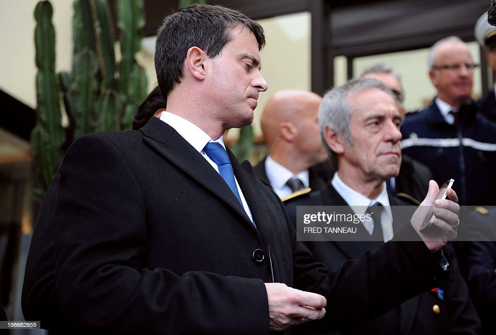 French Interior Minister, Manuel Valls looks at his mobile phone during a visit at the maritime gendarmerie barracks on November, 23, 2012 in Lorient.